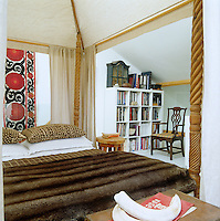 The cushions on the bed, which is covered by a sumptuous fur throw, are Malian mudcloth and the suzani hanging on the wall behind was bought in Portobello Market