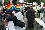 N.C. Pride Parade participants embrace in front of parade protesters in Durham on Saturday, Sept. 29, 2012, at the corner of Main and Broad streets.