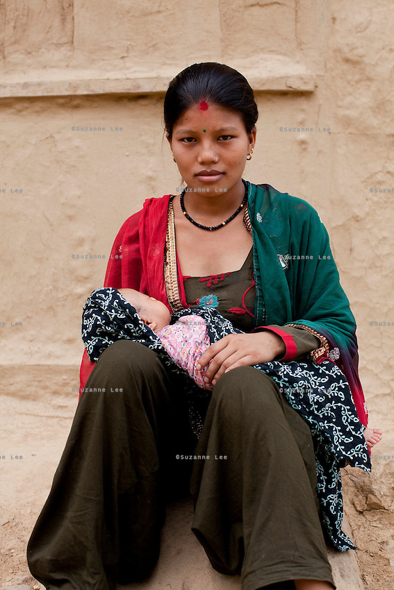 Nisha Darlami, 19, carries her 1 month old baby girl, Bushpa, as she sits in her mother's house in Kalyan Village, Surkhet district, Western Nepal, on 30th June 2012. Nisha eloped with her step nephew when she was 13 but the couple used contraceptives for the next 6 years to delay pregnancy until she turned 18. In Surkhet, StC partners with Safer Society, a local NGO which advocates for child rights and against child marriage. Photo by Suzanne Lee for Save The Children UK