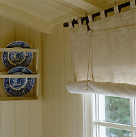 Detail of an embroidered rolller blind and a pair of plates displayed on the wall in the dining room