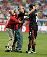 An AC Milan fan who ran out on the field seeks a hug from AC Milan midfielder Ronaldinho (80) while being restrained by security.  AC Milan defeated the Chicago Fire 1-0 at Toyota Park in Bridgeview, IL on May 30, 2010.