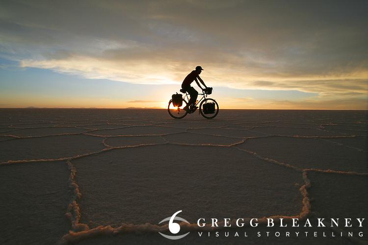 Brook Allen cycles over the Salar de Uyuni at Sunset - Bolivia - South America
