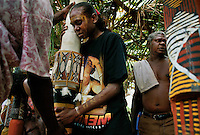 The girl in the photo is grieving for her father as women mourn the dead and cling to poles during a Cleansing ceremony on Tiwi Islands. Culture here seems to be more intact because this place is an island and just more removed from modern western culture.  <br /> A cleansing ceremony is the final ceremony in the death of a family member.  A year or so after the funeral the family paints pukamani poles and places them around the grave.  <br /> In some communities people won't say the name of the deceased or go back into the home until there is a big cleansing rain.  But rituals vary. <br /> Relatives of this family brought pukamani poles from Snake Bay on the other side of the island.  They continued with this ceremony even though there was an impending cyclone.  Even though the ceremony is supposed to be a year or two after the death--often it is held just before Xmas at the beginning of the wet because everyone gets their Xmas club money around that time and there is an exchange of money at the end of the ceremony. The family pays the dancers and totem carvers. <br /> Tiwi has two islands--Bathurst and Melville.  This ceremony is in the town of Garden Point on Melville Island.  Melville Island is 2nd largest island in Australia.