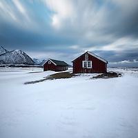 Two red farm sheds below stormy winter sky, Austvågøy, Lofoten Islands, Norway
