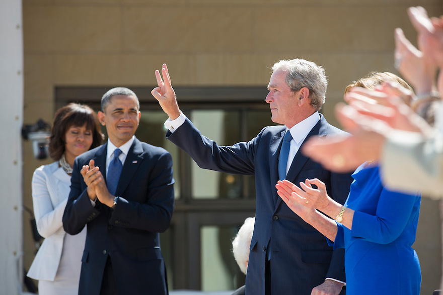 Former President George W Bush gives a W sign at the dedication of the George W. Bush presidential library on the campus of Southern Methodist University in Dallas.    On the left are first lady Michelle Obama and President Obama.