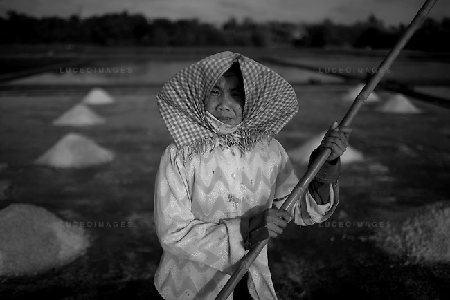 Salt people of Vietnam..Lan Pham, 40, spends four months out of the year with her family working on their salt farm in Ben Tre, about four hours south of Ho Chi Minh City, Vietnam.  The rest of the year Pham works as a maid in the city...Farmers harvest salt cultivated in rice-patty like fields in Ben Tre, a village in southern Vietnam. The salt season usually begins in January and ends in March as these are the driest months. Photo taken Friday, March 21, 2008. Kevin German / kevin@kevingerman.com