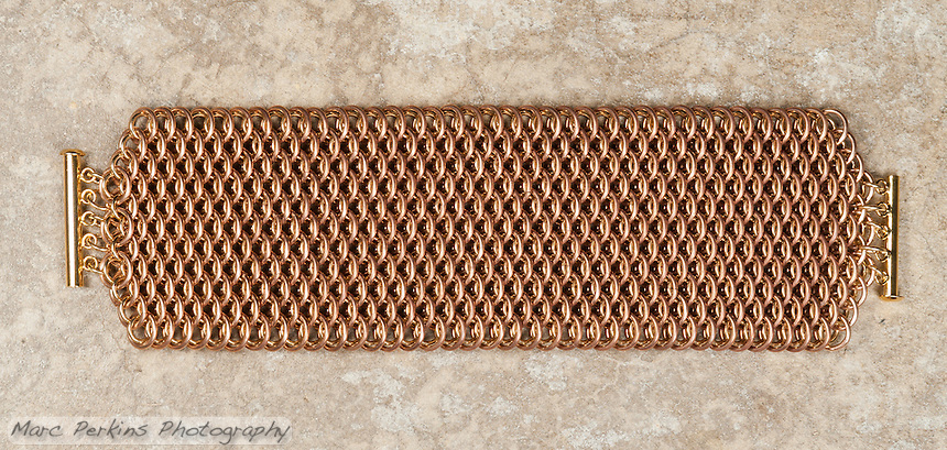 "A brass and bronze dragonscale weave chainmail bracelet.  The maille was made with 18ga 1/4"" bronze and 19ga 11/64"" jeweler's brass, and uses a gold tone slide clasp."