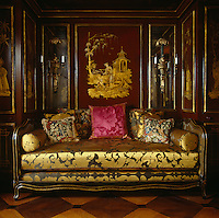 The Chinese boudoir has exotic narrative scenes on its red lacquer panelling and is furnished with a large daybed