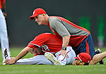 22 July 2012: Washington Nationals Strength & Conditioning Coach John Philbin stretches out Danny Espinosa prior to a game against the Atlanta Braves at Nationals Park in Washington, DC. The Nationals defeated the Braves 9-2 to split their 4-game weekend series. Mandatory Credit: Ed Wolfstein Photo