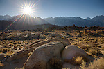 California, east central, Lone Pine. Rock formations in the Alabama Hills recreation area with the sun about tho set over the Sierra Nevada Mountains.