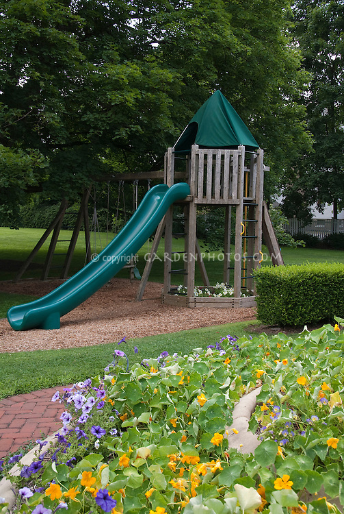 Kids backyard near garden, with tree house, sliding board, tiered plantings of petunias &nasturtiums, trees, shade, swings, boxwood, lawn