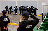 Mexico City, Mexico<br /> June 16, 2008<br /> <br /> Secretary of Public Security Genaro Garcia Luna, Mexico's President Felipe Calderon and Interior Minister Juan Camilo Mourino watch as a SWAT teams demonstrate their maneuvers during the opening of a new federal police center. The first of ten scheduled to open around the country.