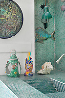 A detail of a blue and white bathroom tiled in mosaic tiles. A washbasin is created in the tiles. Several ceramic pieces with a fish theme are placed around.