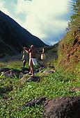 Hawaiian man walking into Waikolu valley with fish and gourd,Molokai