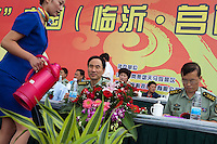 Local PLA (People's Liberation Army) officials are served tea as they watch the Red Games. Held in Junan County, this sporting event is a nostalgic tribute to the communist era.
