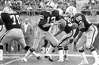 "Oakland Raider QB Kenny ""The Snake"" Stabler drops back to pass. Protection by Henry Lawarence #70 and Clarence Davis #28. (1977 photo by Ron Riesterer)"