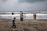 Tourists are enjoying the evening at the Silver beach Cuddalore while a local fisherman walk passes them. Silver beach is one of the most affected areas due to 2004 Tsunami. Tamil Nadu, India