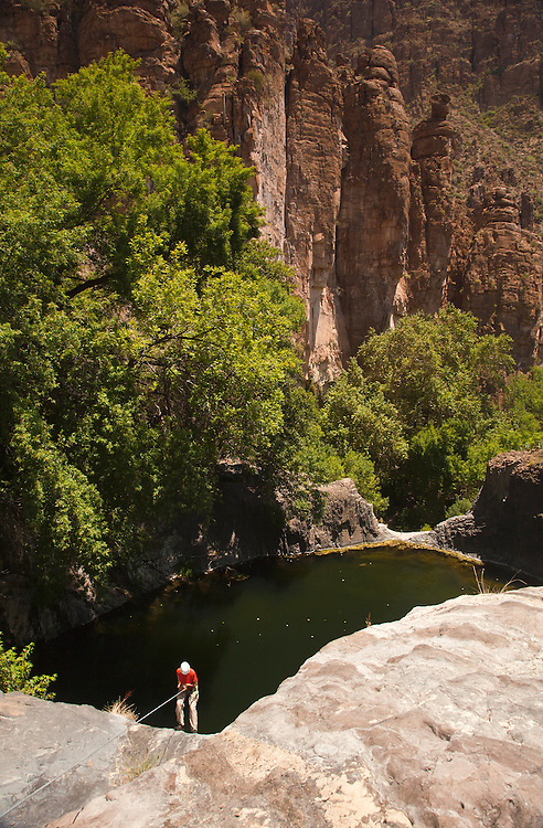 Surrounded by volcanic spires, Jacque Miniuk rappels into the 5th and final pool found within Devils Canyon near Superior, Arizona.