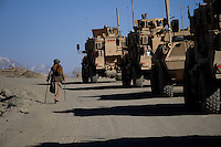 Disabled  Afghan man walking past MRAP convoy  in Wardak Province - March 2009- on patrol with the US 10th Mountain Division in Maidan Shah provincial town centre
