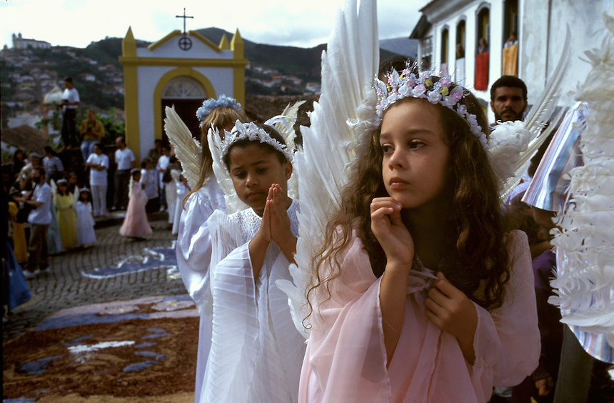 Marching up the hilly streets of Ouro Prêto, a young angel watches the passing crowd during the resurrection procession of Easter morning.