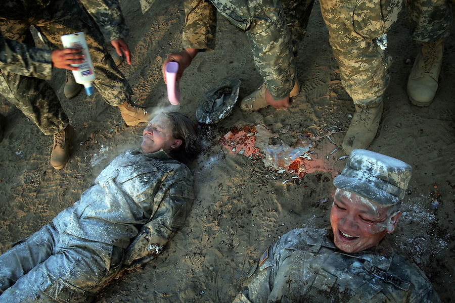 Following a promotion ceremony, two Charlie Med promotees are doused in shampoo, foot powder, sun tan lotion and other assorted hygiene products by way of initiation at Camp Ramadi, Iraq on Sunday Oct. 01, 2006.