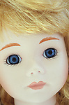 Close up of face of contemporary girl doll with innocent face and stereotypical big blue eyes and long blonde hair