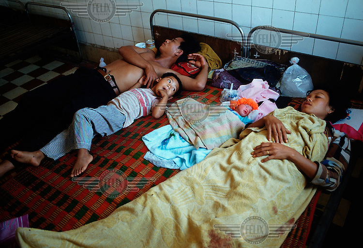 Family in a city maternity ward, as the son looks over towards his mother and his newborn sibling