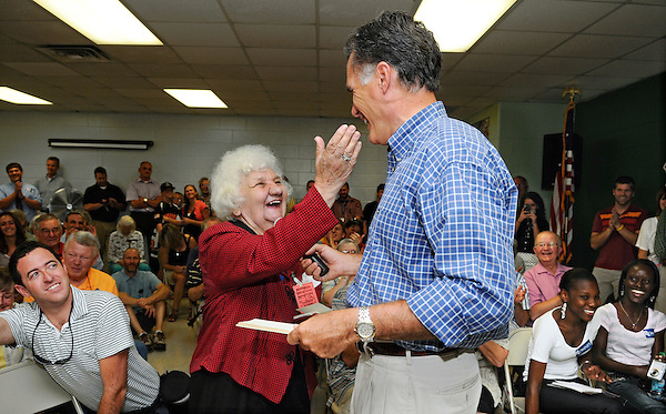 Keene, New Hampshire: August 24, 2011<br /> Lucy Opal, 83, prepares to caress the cheek of presidential candidate Mitt Romney during a campaign town hall meeting. She was delighted when Romney signed her autograph book that contained an autograph from 1969 of Romney's father George Romney, a former politician. This event happened at the Keene Recreational Center. &copy;Chris Fitzgerald / Candidate Photos