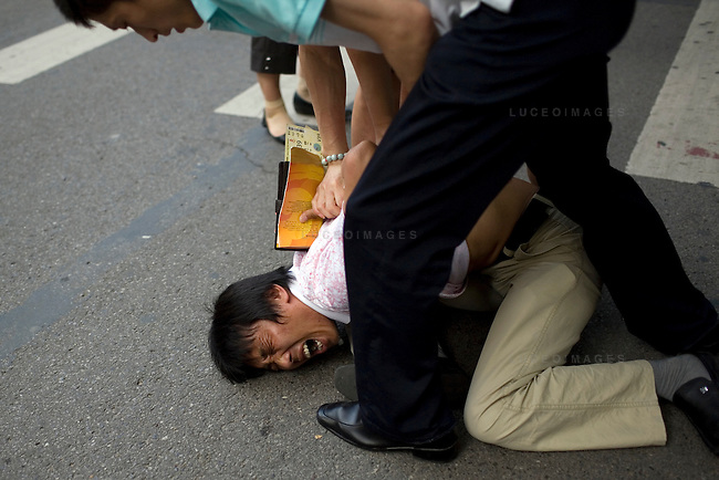 Two secret police wrestle with a scalper during an arrest outside of Worker's Stadium in Beijing, China on Monday, August 18, 2008.  Kevin German