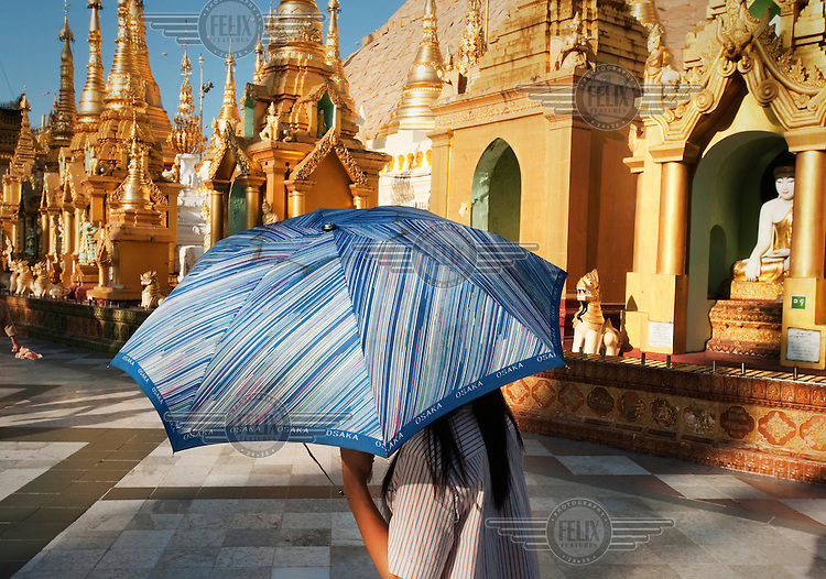 A woman protects herself from the sun with an umbrella at the base of the Shwedagon pagoda in Yangon.
