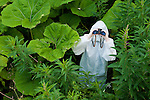 Boy in protective suit and mask in the wilds with binoculars, Scotland