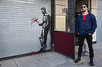 "Street art enthusiasts flock to Larry Flynt's Hustler Club in the Hells Kitchen neighborhood of New York on Thursday, October 24, 2013 to see ""Waiting in vain""  the twenty-fourth installment of Banksy's graffiti art. The stenciled artwork is on the roll-up gate at the entrance to the gentlemen's club, which has posted security guards outside to protect their new masterpiece.  The elusive street artist is creating works around the city each day during the month of October called ""Better Out Than In"".  (© Frances M. Roberts)"