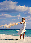 Young Caucasian woman on the beach in a white sun dress with a shawl blowing in the breeze.