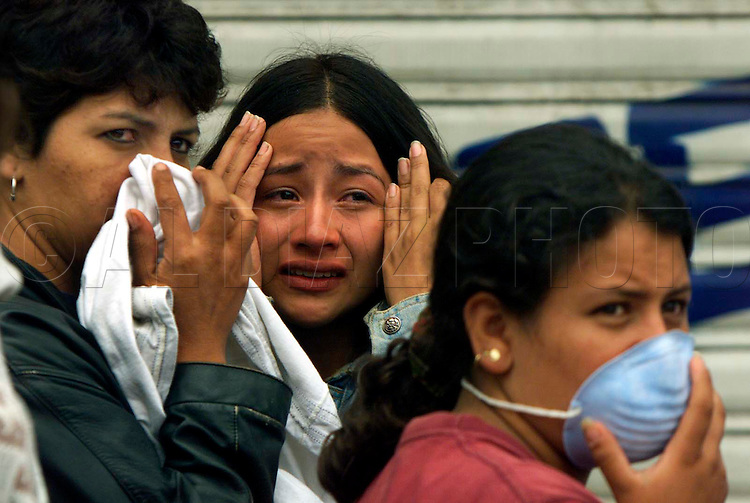 1/28/98 Al Diaz/Herald staff--l to r are, Aydee Gutierrez, Ludivia Vargas, Paola Andrea.<br />Vargas reacts after her husband was found buried inside their apartment in Armenia. The women on either side are friends watching the search for more victims.
