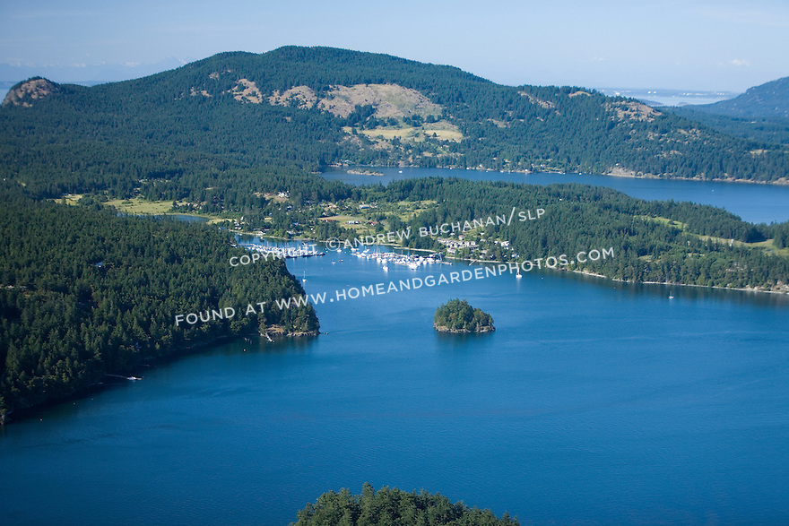 Orcas Island, WA in the San Juan Islands, as seen from the air on a sunny summer late afternoon.  At the center of the image cluster boats at Deer Harbor Marina / Resort in the body of water known as West Sound, while the long, skinny body of water behind is East Sound.  Mt. Constitution, the highest point in the San Juans, rises behind.