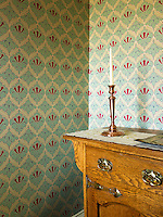 Close up of a single candlestick on an antique candelabra in the bathroom of a restored Georgian country house with wallpaper by Robert Kime