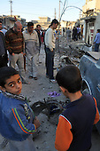 KIRKUK, IRAQ: A child looks up at the camera at the scene of triple car bomb attack...At 6 am, three car bombs detonated in the peaceful Kurdish neighborhood of Imam Kasimin Kirkuk.  There were 17 casualties.  Kirkuk is Iraq's most ethnically mixed city and is one month away from a volatile census that will determine the future of the city...Photo by Ari Mohammad/Metrography.