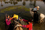 Children in the Iraqi village of al-Radathiya gather water at a river, one of two sources of water for their approximately 11,000 population village, east of Najaf. The river is a kilometer from the village and the water has left many of the villagers with cholera and chronic diarrhea. According to their $680 million, no-bid, contract, Bechtel Corporation is responsible for providing potable water to southern Iraq.