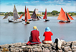 Tourists watch the boats as they warm up for the racing at the Cruinniu na mBad Festival in Kinvara. Photograph by John Kelly.