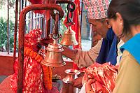 Kathmandu, Nepal.  Hindu Priest Applying Sindur Powder to Bust of the Hindu God Hanuman in a Neighborhood Temple.