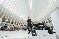 A worker cleans the stage between entertainment in the World Trade Center Transportation Hub, known as the Oculus, on Tuesday, August 16, 2016 during the grand opening festivities for the retail spaces. The 350,000 square foot retail space will feature over 100 stores when they all open, including a now opened Apple Store. The mall opens almost 15 years after the World Trade Center terrorist attack.  (© Richard B. Levine)