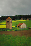 Old brick tower used as electrical sub station and new wooden farm building in German countryside. showing crops of oilseed rape and freshly ploughed field. Aschaffenburg, Germany.