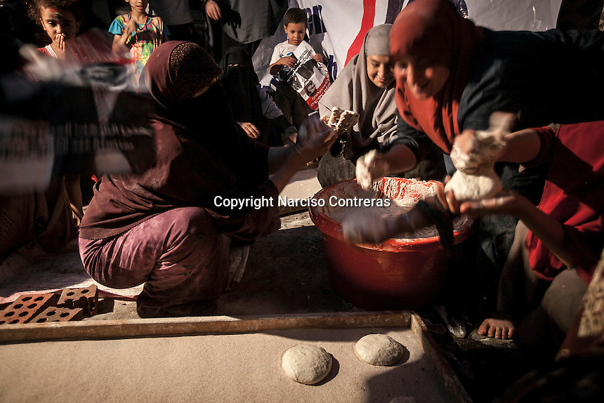 In this Friday, Aug. 09, 2013 photo, women supporters of the ousted president Mohammed Morsi cook bread to distribute to the crowd at the sit-in Cairo University in the Giza district of Cairo. (Photo/Narciso Contreras).