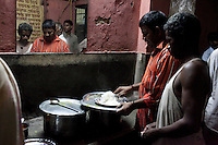 Men buying food in the corridor during the night shift (7pm -7am) at the Aashray Adhikar Abhiyan (AAA) Activity Center for homeless people on 4th October 2010, in Old Delhi, India. Picture: Suzanne Lee for The Australian.