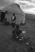 A family near their yurt, on the land which they work in the summer months, near Lake Issyk-Kul,  Kyrgyzstan.