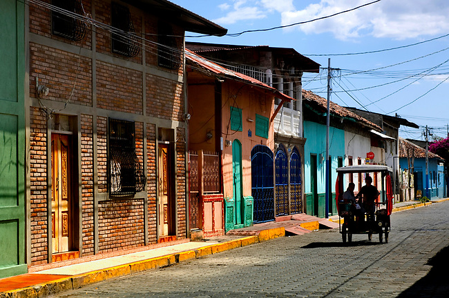 Colorful 19th century wooden row houses and three wheel taxis are a common sight in the Pacific port town of El Corinto, Nicaragua.