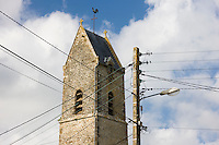 Telephone and power wire cables on telegraph pole in front of church in Houesville, Normandy, France