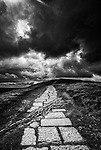Stone path leads to the ancient Man Tor in Edale, Peak District, England