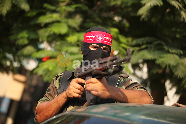 A masked Palestinian militant of the National Resistance Brigades, a group linked to the Democratic Front for the Liberation of Palestine holds his weapon during a military parade against the killing of a 18-month-old Palestinian toddler Ali Dawabsheh in Duma village, in Gaza city on July 31, 2015. The Palestinian toddler was burned to death and four family members injured in the arson attack on two homes in the occupied West Bank. Photo by Ashraf Amra