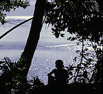 Boy sitting on the shore looking out to sea, Fiji, South Pacific,